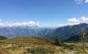 Aussicht auf Wiesen und Berge unter Himmelblau.