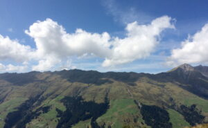 Auf der anderen Seite des Grats werfen große Wolken ihre Schatten auf die Berglandschaft.