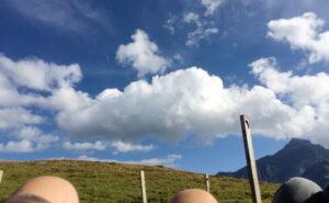Etwa auf halber Abstiegstrecke finden wir einen Steg, der an den einstigen Lüschersee erinnert, welcher Anfang zwanzigstes Jahrhundert entwässert worden ist. Wir ruhen uns auf dem Steg aus. Im Vordergrund unsere Kniespitzen, die die Bergspitzen grüßen. Vor uns endlose Wiese, rechts ein Berg, darüber wolkiges Himmelblau.