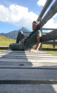 Irgendlink der vor dem Piz Beverin auf dem Steg sitzt und sich am Geländer anlehnt.