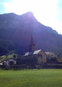 Die St. Martinskirche in Zillis von weitem. Im Hintergrund Berge, vorne Wiese.