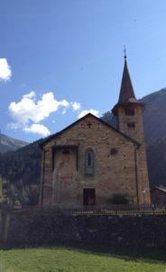 Die Kirche von unten. Die Wandbemalung zeigt den heiligen Christophorus. Im Hintergrund Berge und Blauhimmel.