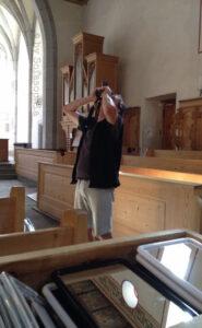 Irgendlink fotografiert die Decke der hölzernen Kirche. Im Vordergrund eine Kiste mit Spiegeln, mit denen die Besucherinnen und Besucher die Decke ohne steifen Nacken betrachten können.