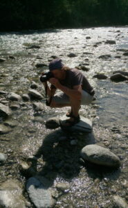 Irgendlink, der auf einem Stein im Fluss hockend einen Steinturm fotografiert.
