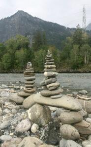 Beide Steintürme vor dem fließenden Rhein. Im Hintergrund das andere bewaldete Ufer, Berge, Himmel.