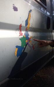Eine Zeigefinger von rechts im Bild zeigt auf eine an die Autowand geklebte Europakarte, in welcher alle Länder bunt eingefärbt sind, die unsere Gastgeberin und unser Gastgeber bereits bereist haben.