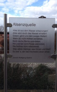 Alsenzquelle-Infotafel mit Gedicht von Goethe über Quellen, am Wegrand stehend