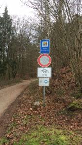 Schilderstange mit Fahrverbot, Raderlaubnis u. a., im HIntergrund der Wanderweg in den Wald