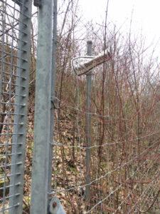 An der Autobahn ein Zaun mit verbogener Warntafel