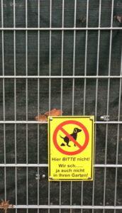 Tafel an Gittertür verbietet Hunden das Scheißen