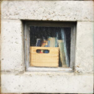 Kirchenfenster von außen, das mit Kisten und Büchern vorgestellt ist