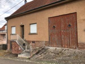 Altes Haus mit Scheune, die zwei verschlossenen Fenster und die kleinen Fensterchen des Scheunentors wirken wie zwei Gesichter nebeneinander.