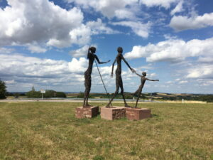 Drei menschliche Skulpturen aus Draht auf roten Betonsockeln, auf Wiese unter wolkigem Blauhimmel: ein Kind und zwei Erwachsene