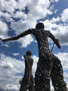Zwei Skulpturen von hinten vor wolkigem Blauhimmel