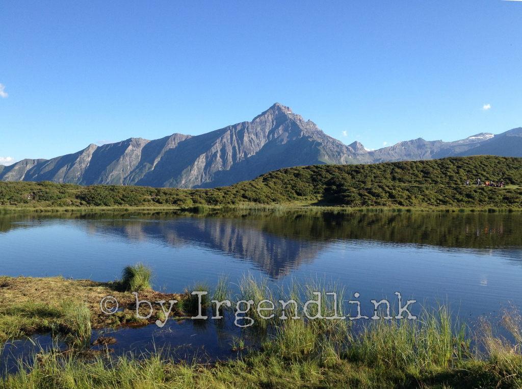 Wieder der Bergsee mit Bergmassiv im Hintergrund, vorne und drumrum Wiesen