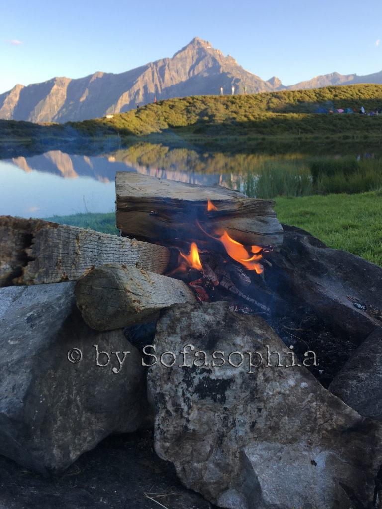 Feuerstelle vor See und Bergmassiv