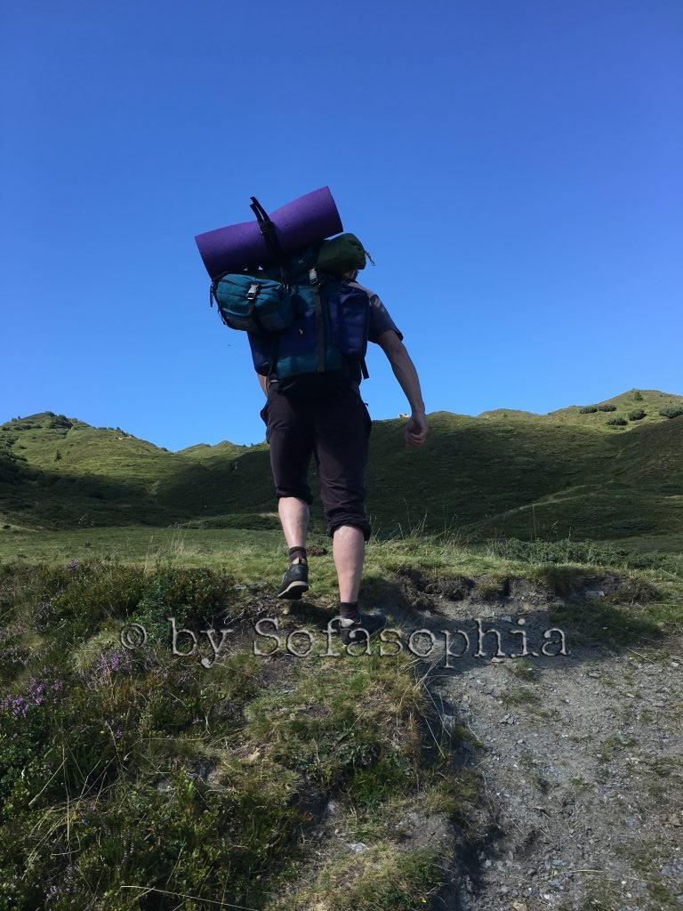 Irgendlink mit Wanderschuhen und großem Rucksack von hinten beim Aufstieg