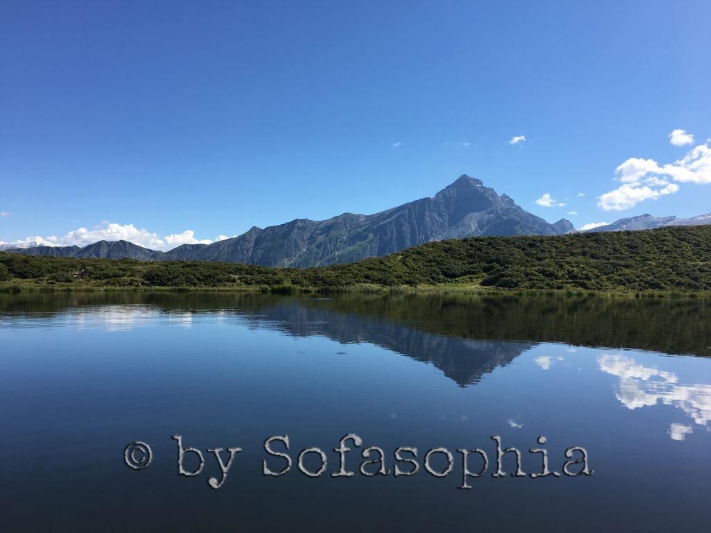 Bergsee vor Bergmassiv unter Blauhimmel
