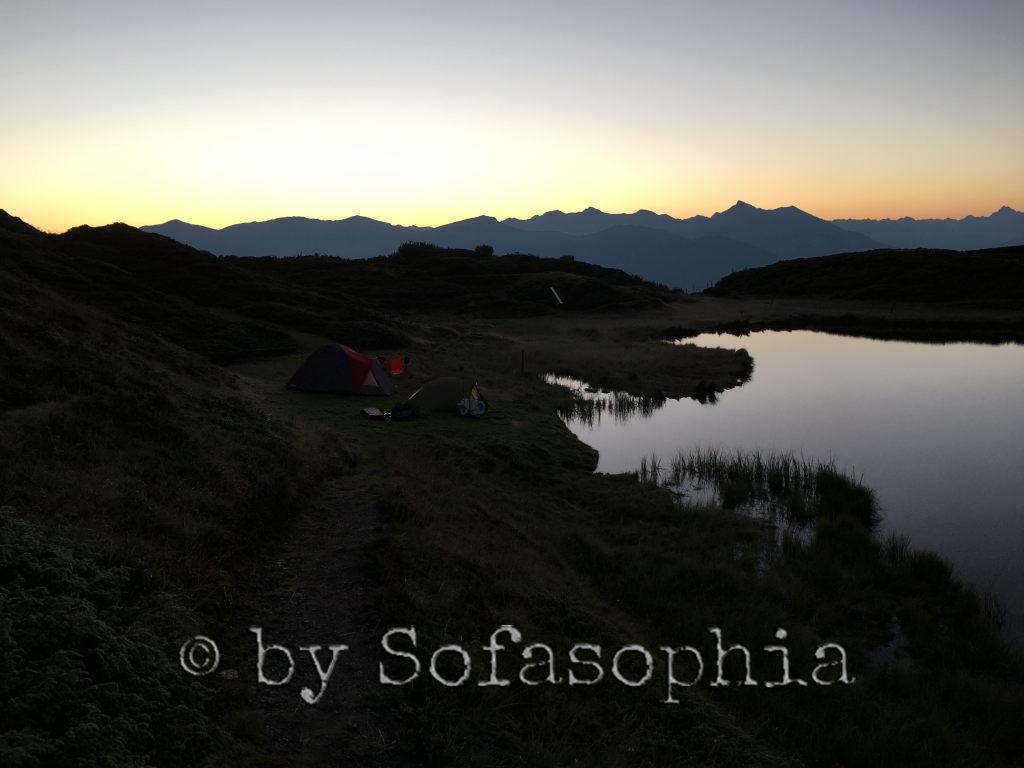 Vor dem Sonnenaufgang: See, Berge. Alles im Dämmerlicht, hinten ein erster orangefarbener Streifen