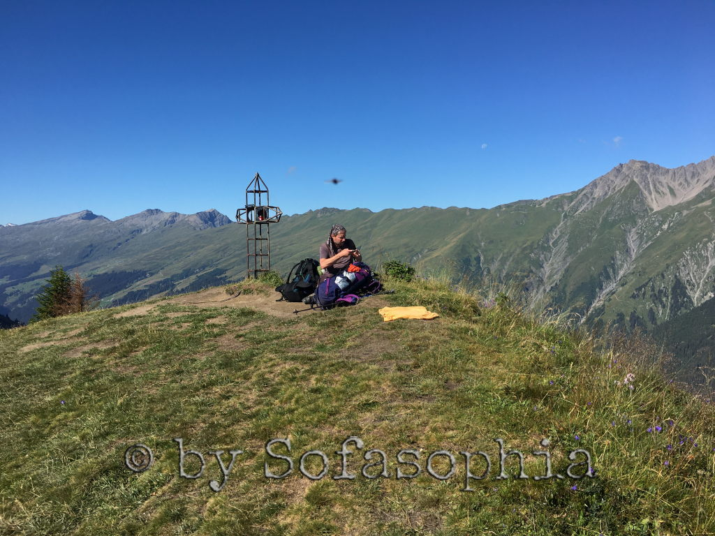 Irgendlink sitzt auf dem Tguma am Boden auf der Wiese und betrachtet seine Aufnahmen im Handy. Hinter ihm das Gipfelkreuz.