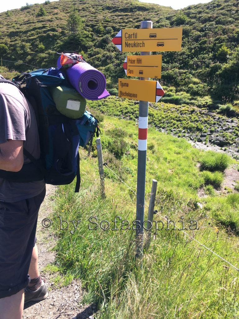 Beim nächsten Wegweiser steigen wir abwärts. Im Bild die Wegweiser und Irgendlinks Rucksack.