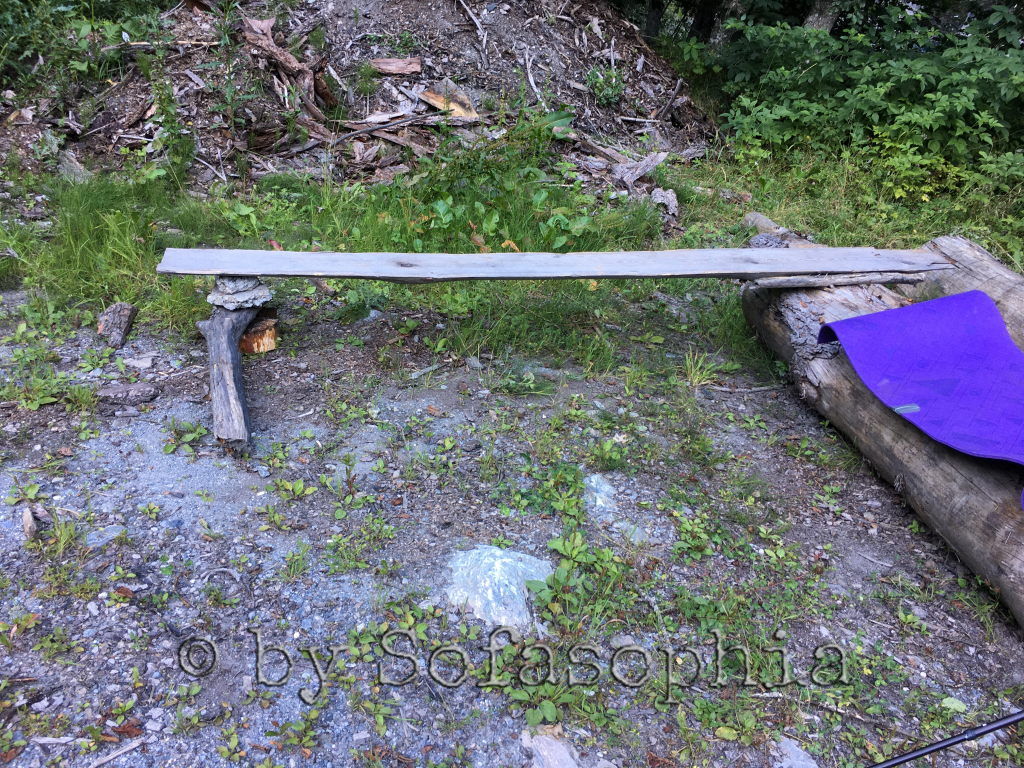 Wir improvisieren aus einem Brett und Steinen eine Sitzbank bei einem Holzlagerplatz, wo wir später unser Zelt aufbauen.