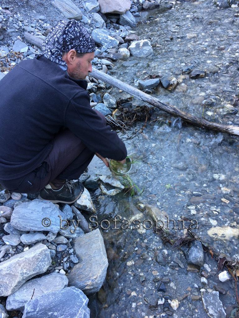 Nach dem Essen spült Irgendlink am Bergbach, der gleich nebenan in den Stausee fließt, den Topf mit einem Grasbüschel und Wasser.