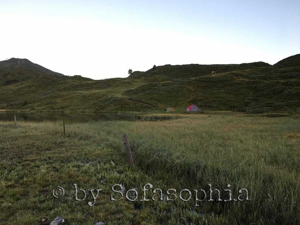 Blick von unten auf den See, den Hügel darum und das Zeltlager mit unserm Zelt und dem unserer beiden Nachbarinnen.