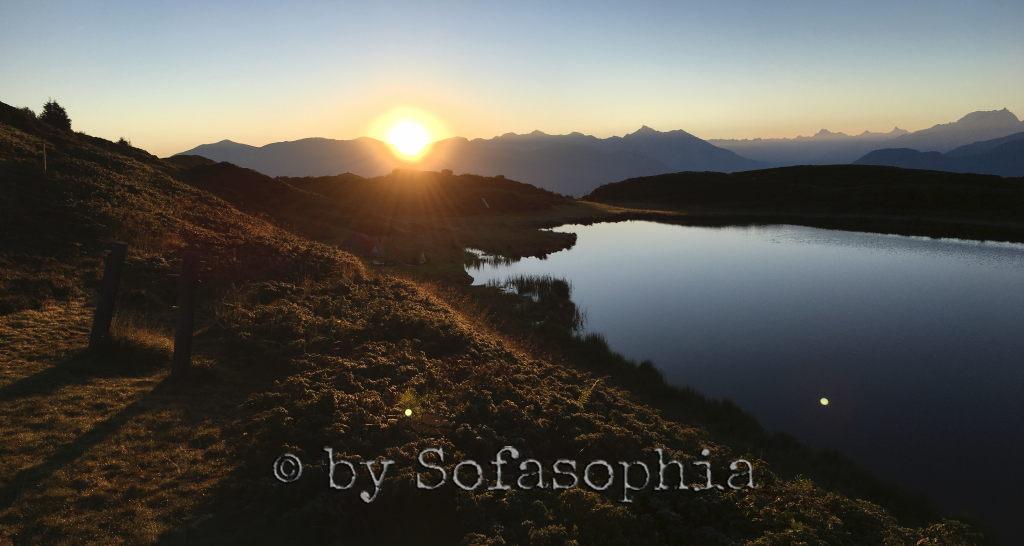 Sonnenaufgang vom Hügel oberhalb des Sees. Die Sonne taucht alles in goldenes Licht, der See glänzt.