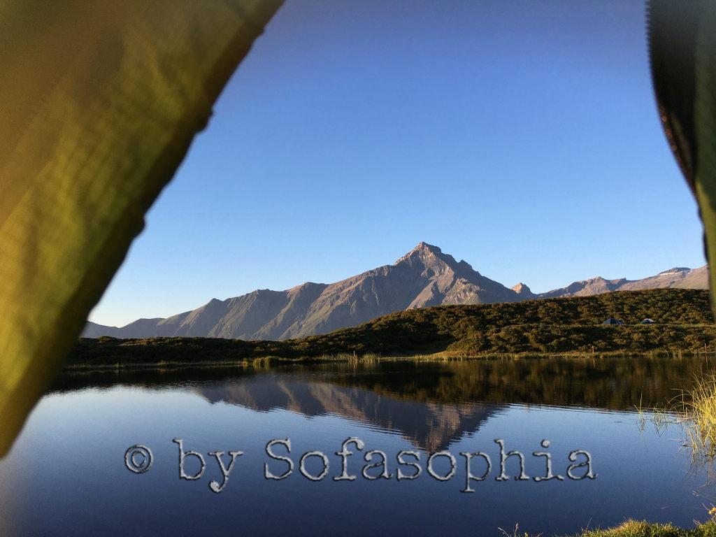 Blick aus dem Zelt auf den See und das Bergmassiv dahinter. Spiegelungen im See.