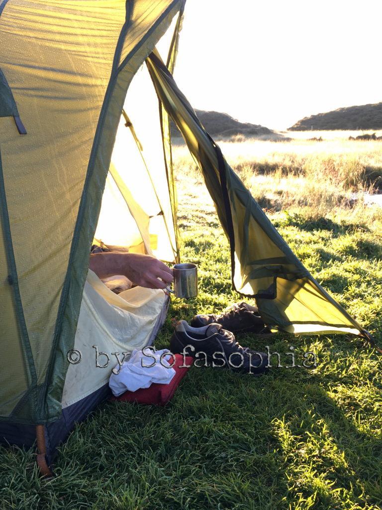 Auch das Zelt ist nun in der Sonne. Irgendlinks Hand greift nach der Kaffeetasse, die vor dem Zelt steht.