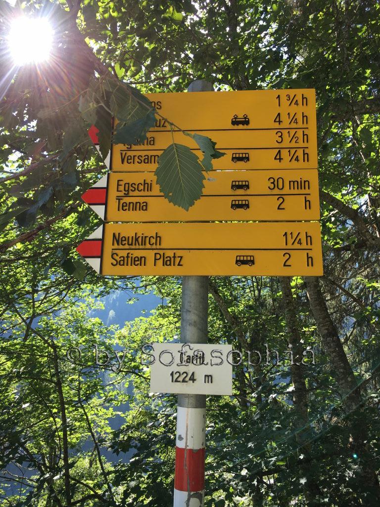 Bei der Postautostation steht unter Bäumen ein Wanderwegweiser mit den umliegenden Zielen.