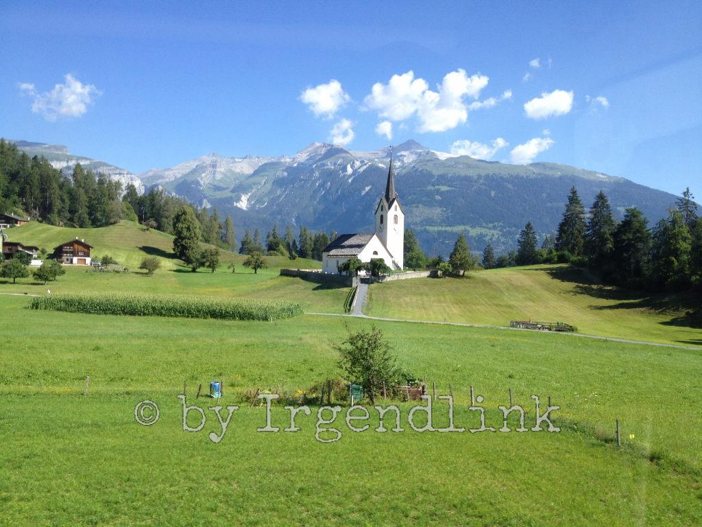 Kirche Versam, vom Postauto aus fotografiert. Vorne Wiesen, hinten Gebirge, darüber Blauhimmel.