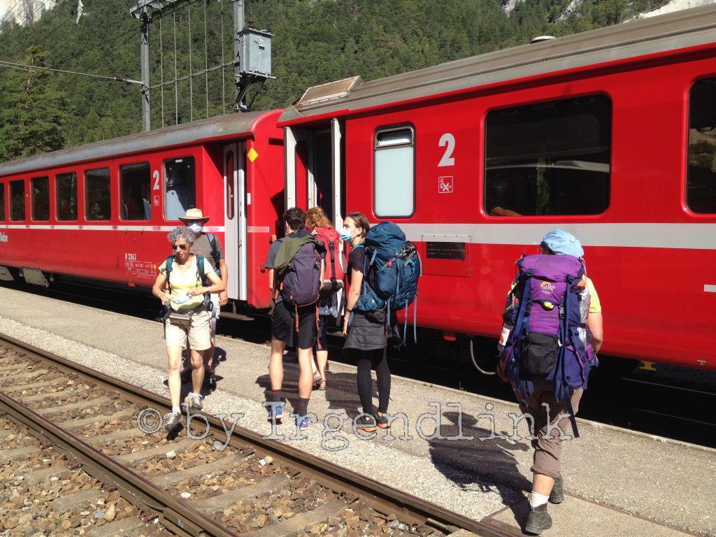 Der rote Zug der Rhätischen Bahn nach Reichenau-Tamins ist eingefahren. Menschen steigen ein und aus.