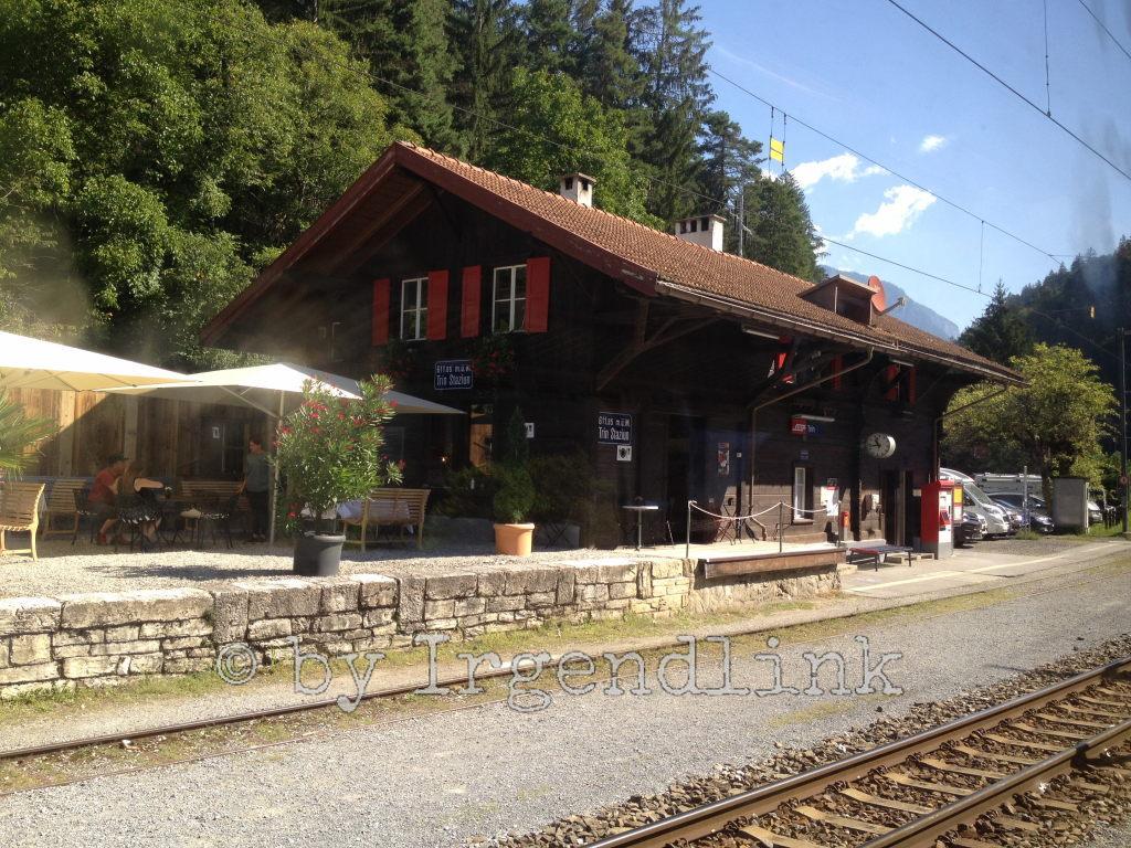 Station Trin, vom Zug aus fotografiert. Auch hier wieder ein Gebäude, das wie ein Wohnhaus aussieht. Dahinter Bäume.