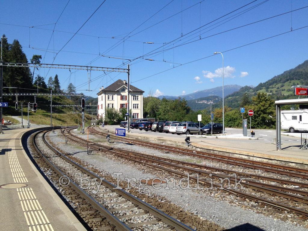 Bahnhof Reichenau-Tamins: Warten auf den Anschlusszug nach Thusis. Vorne Schienen, hinten Gebäude, darüber Drähte und Blauhimmel.