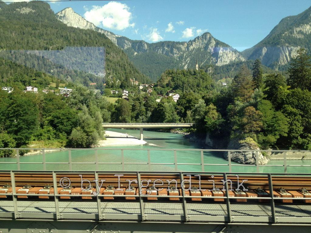 Wir überqueren den Rhein, der sich hier aus Vorder- und Hinterrhein zusammensetzt. Blick auf Brücke, dahinter Flüsse, Bäume, Berge und Blauhimmel.