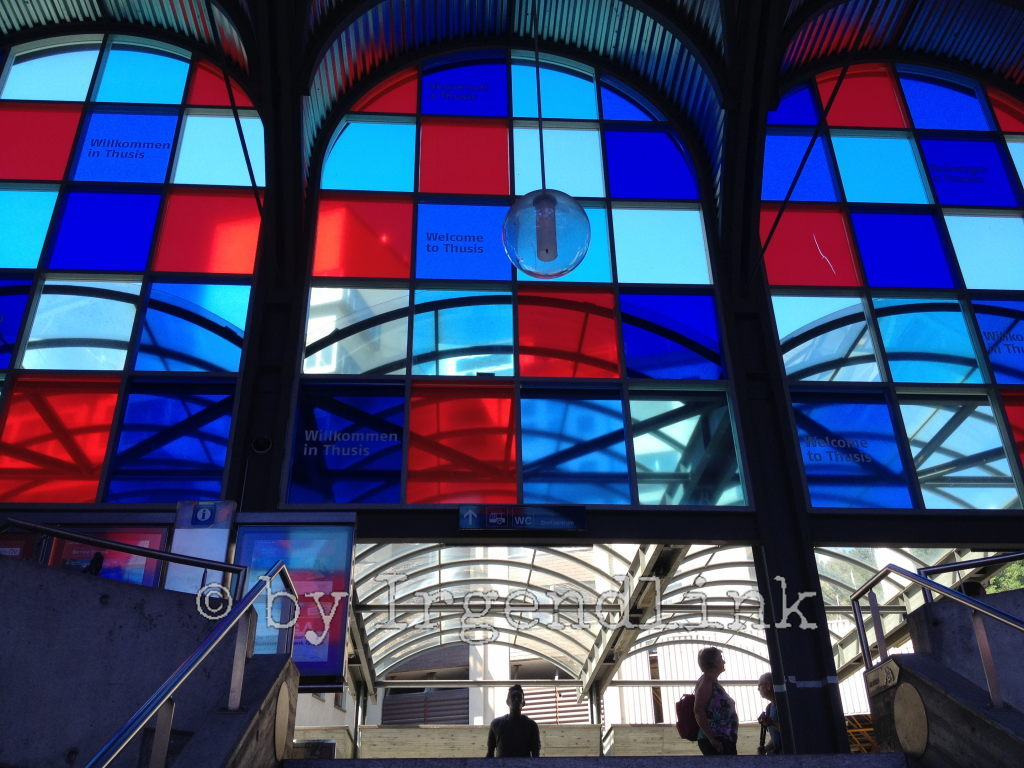 Fensterfront im Bahnhof Thusis aus roten, hell- und dunkelblauen Quadraten, darunter wartende Menschen. Von unten, die Treppe hoch fotografiert.