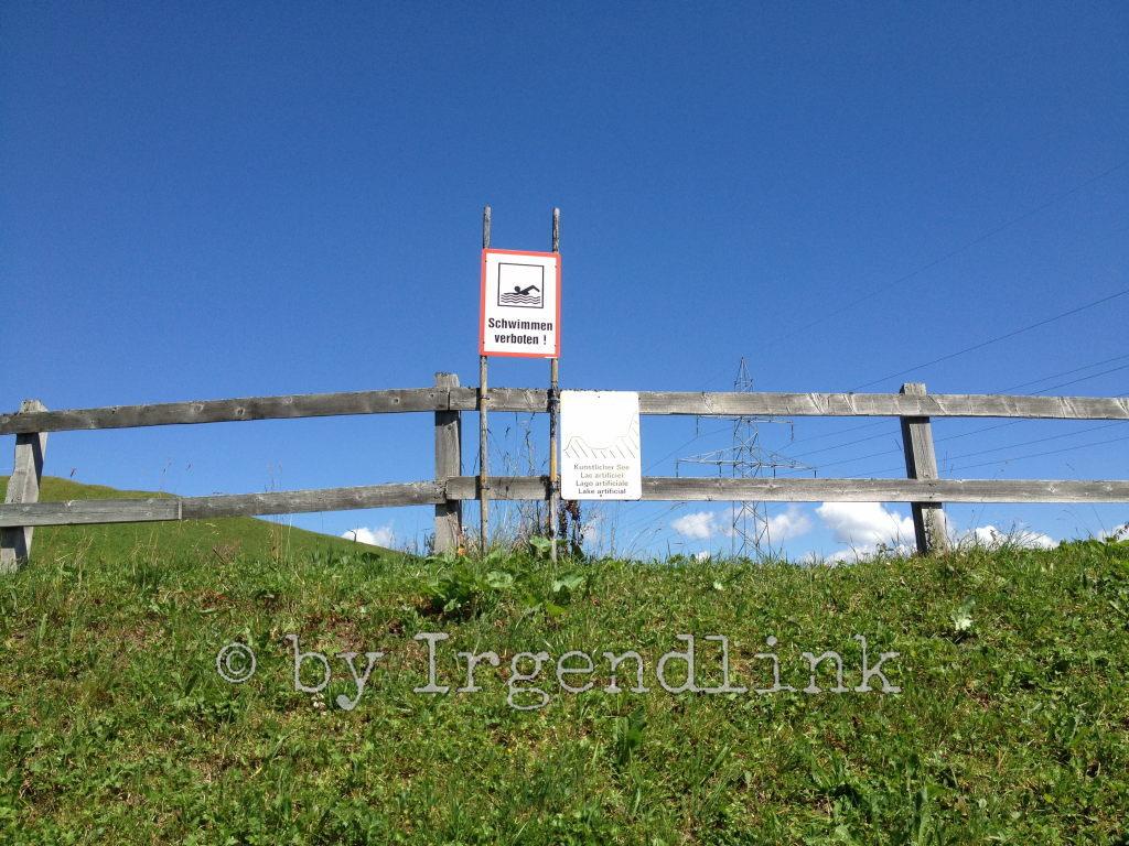 Wir erreichen in der Nähe der Skiliftstation einen künstlichen See, was wir den Tafeln am Zaun entnehmen.