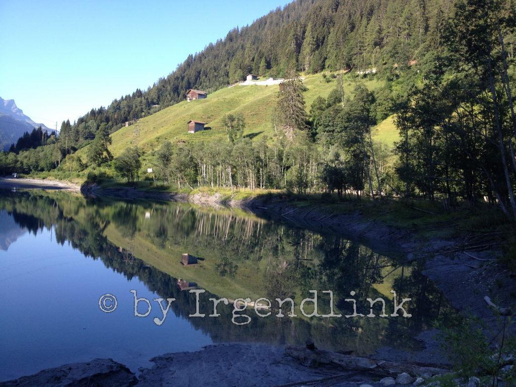Am Stausee ein Blick in die Hügel. Alphütten auf den Wiesen. Darüber Wald. Alles spiegelt sich im See.