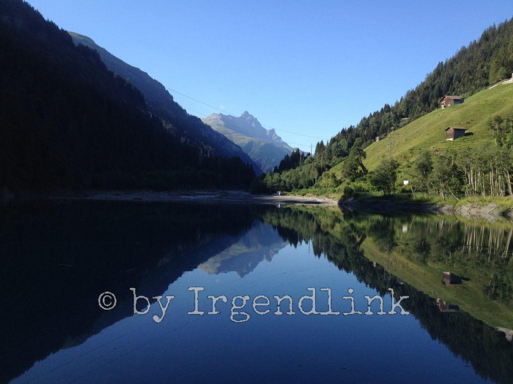 Noch ein Blick auf den Stausee und in die Hügel. Alphütten auf den Wiesen. Darüber Wald. Alles spiegelt sich im See.
