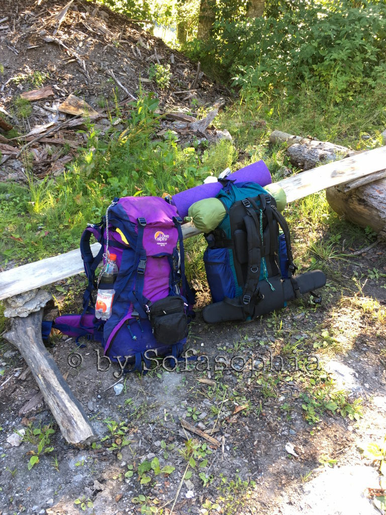 Die zwei fertig gepackten Rucksäcke lehnen an der provisorischen Sitzbank.
