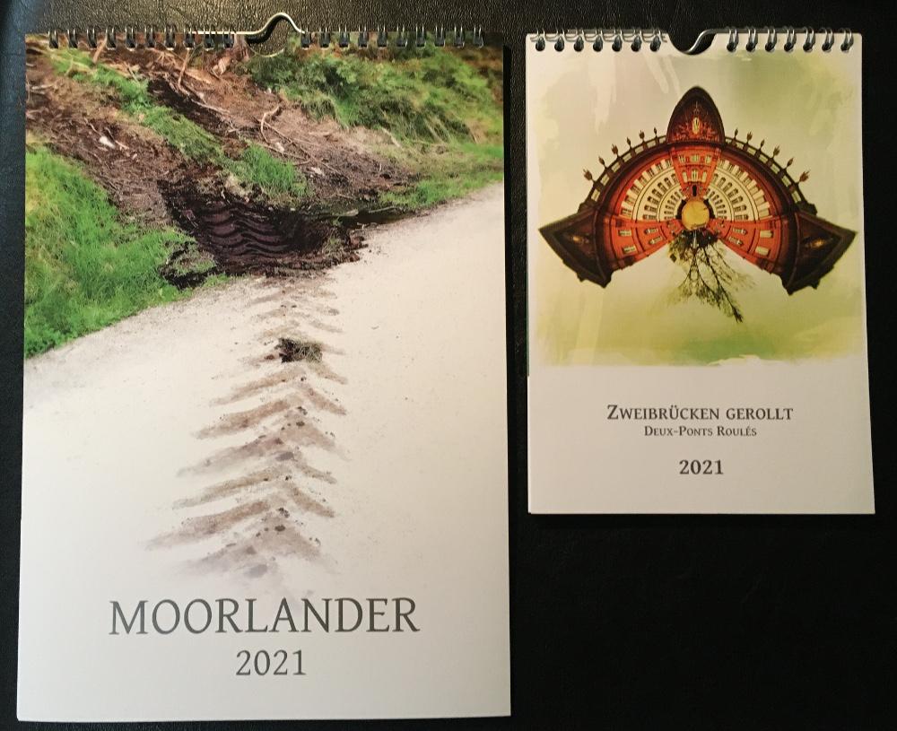 Der neue Moorlander-Kalener 2021 und der Zweibrücken gerollt-Kalender 2021 nebeneinander auf schwarzem Hintergrund.