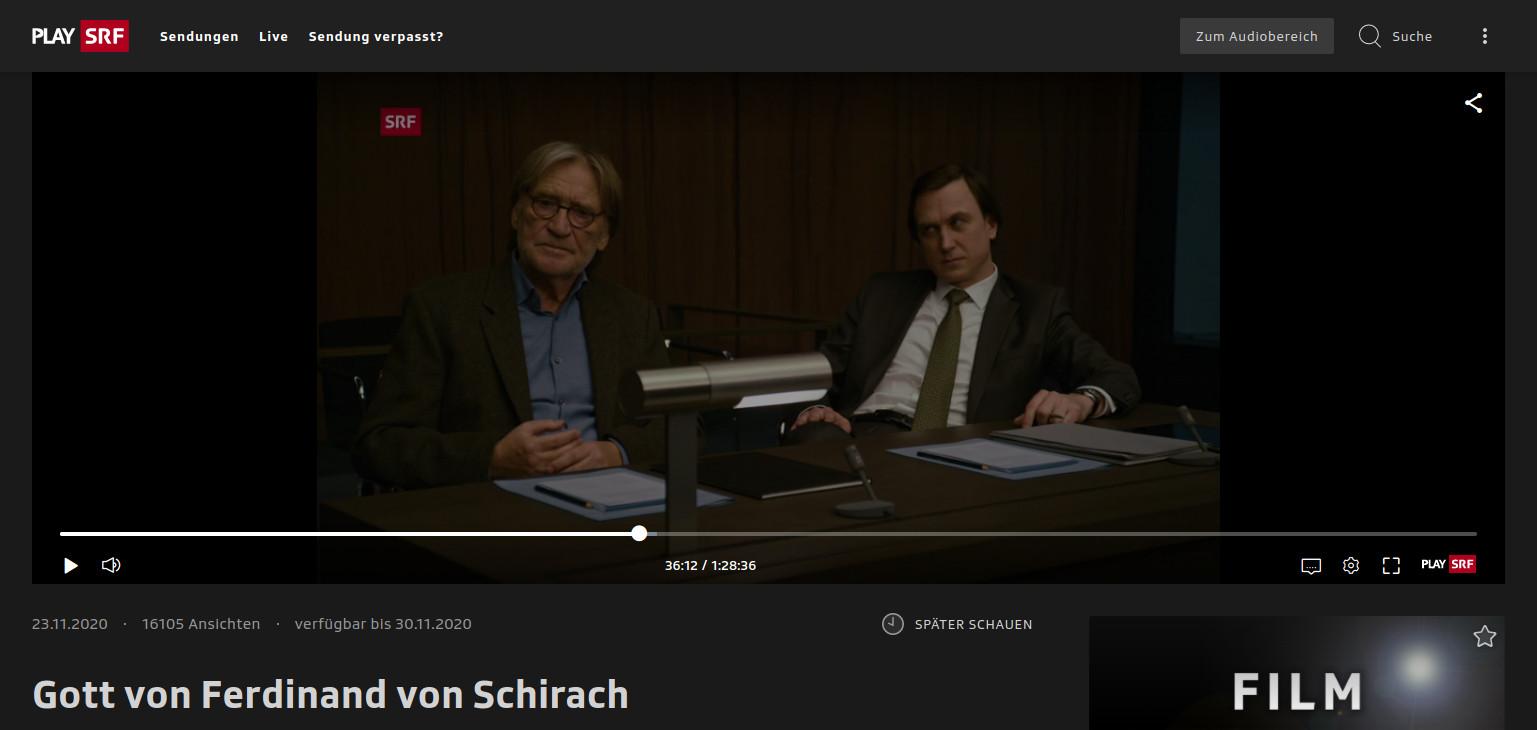 Screenshot einer Filmszene aus dem besprochenen Film. Links im Bild der Antragsteller Richard Gärtner, rechts im Bild sein Anwalt. Sie sitzen an einem Tisch, schauen nach vorne links und hören aufmerksam jemandem zu.