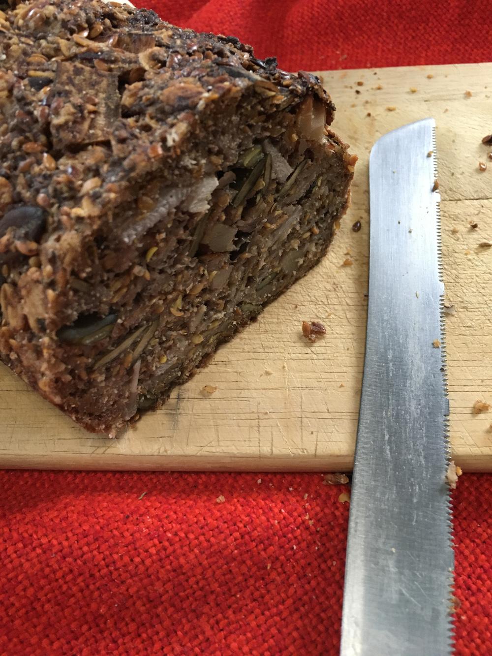 Dunkles Körnerbrot auf Holzbrett auf rotem Tischtuch, rechts ein Brotmesser parallel zum rechten Bildrand