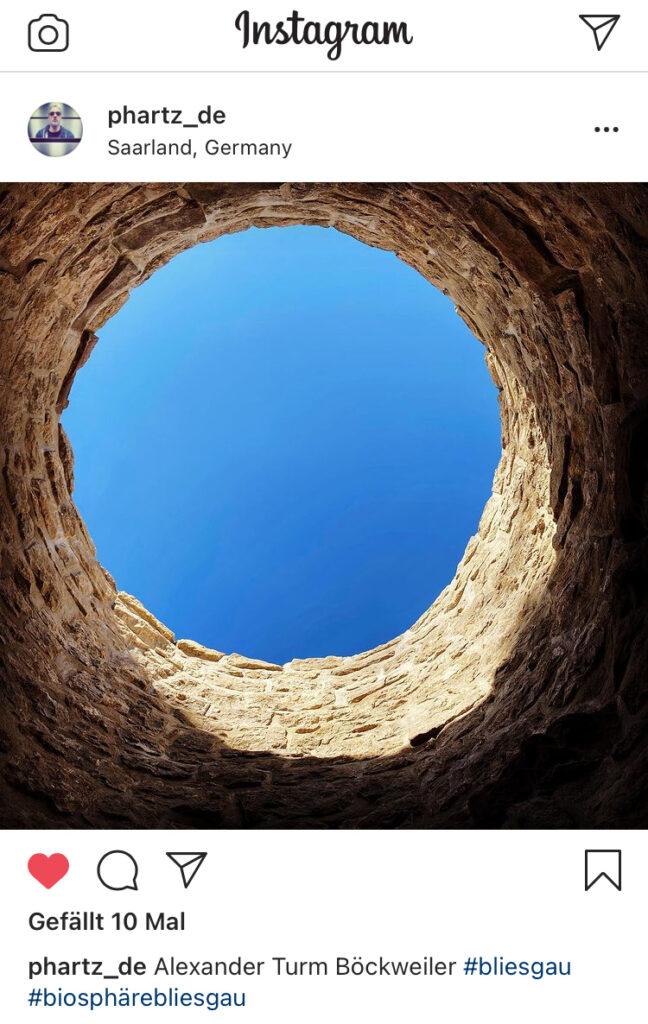 Screenshot eines Instagram-Beitrages, das den Blick von unten nach oben zum Himmel zeigt. Am Rand ist der kreisrunde Mauerrest des alten Turms zu sehen.