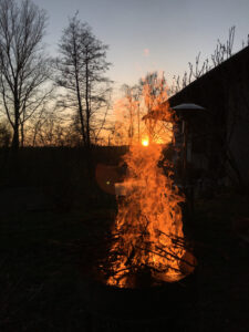 Sonnenuntergang, Bäume, Scheune und das Feuer im Vordergrund