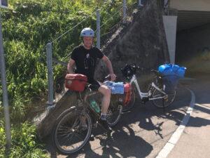 Irgendlink mit Helm und vollgepacktem Rad, mein Rad im Hintergrund