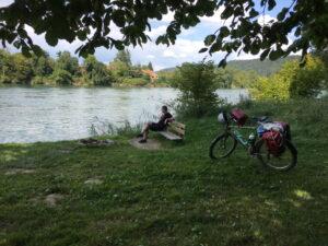 Am Rhein. Irgendlink auf einer Bank. Im Hintergrund Fluss und Bäume.