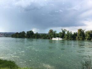 Ein Boot auf dem Rhein. Blauhimmel mit ersten Gewitterwolken.